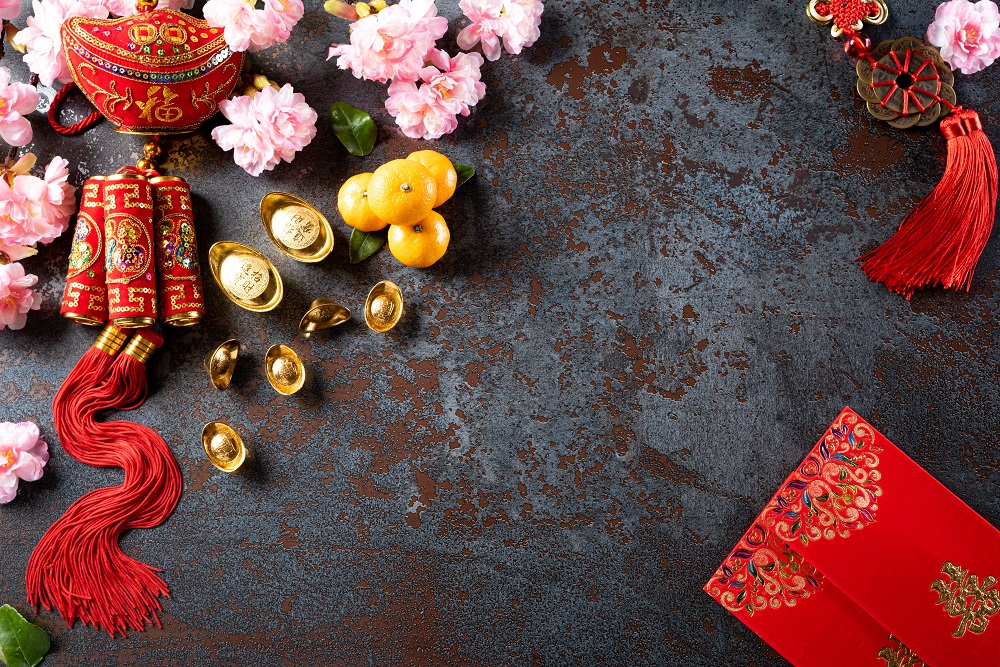 Chinese new year festival decorations pow or red packet, orange and gold ingots or golden lump on a black stone texture background. Chinese characters FU means fortune good luck, wealth, money flow.